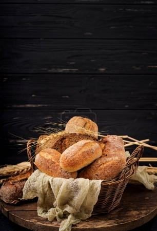 Photo for Assortment of baked bread in basket on wooden background with copy space - Royalty Free Image