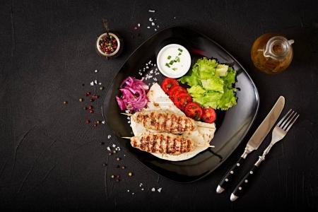 Minced Lula kebab grilled turkey with fresh vegetables on plate
