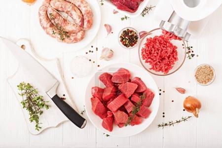 plates with chopped raw meat and homemade sausages with meat grinder on table, concept of   process of preparing forcemeat