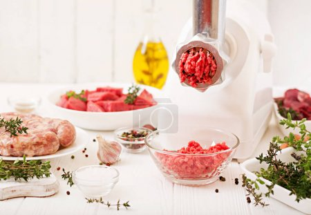 Photo for Plates with chopped raw meat and homemade sausages with meat grinder on table, concept of   process of preparing forcemeat - Royalty Free Image