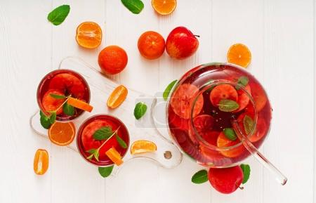 Sangria with fruits and mint on a white background. Top view