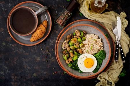 Healthy breakfast. Oat porridge, egg and salad of baked vegetables - mushrooms and Brussels sprouts. Healthy lifestyle. Top view