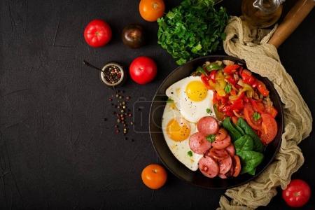 Le petit déjeuner. Œufs frits avec saucisses et aux légumes dans une poêle sur un fond noir dans un style rustique. Vue de dessus
