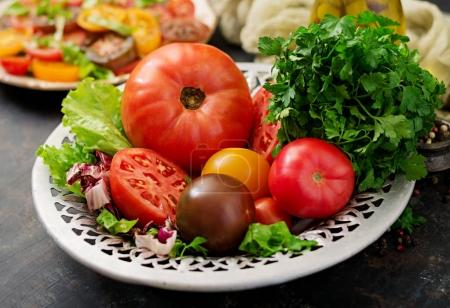 Tomatoes of different colors with green herbs in a bowl on a black background