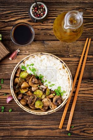 Photo for Vegan menu. Dietary food. Boiled rice with mushrooms and Brussels sprouts in Asian style. Top view. Flat lay. - Royalty Free Image