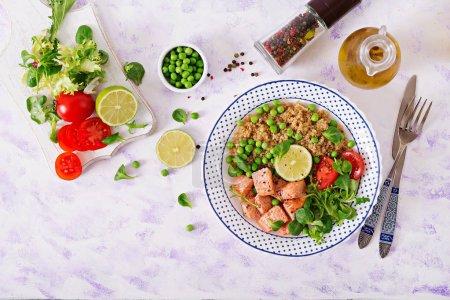 Photo pour Dîner sain, tranches de saumon grillé, quinoa, pois verts, tomates, lime et feuilles de laitue - image libre de droit