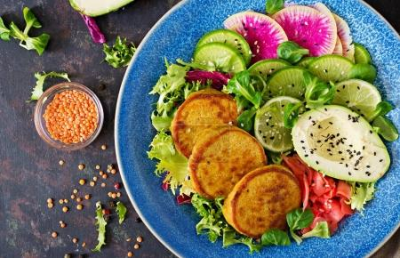 Vegan buddha bowl dinner food table. Healthy food. Healthy vegan lunch bowl. Fritter with lentils and radish, avocado salad. Flat lay. Top view
