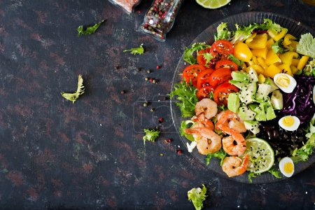 Healthy salad plate. Fresh seafood recipe. Grilled shrimps and fresh vegetable salad - avocado, tomato, black beans, red cabbage and paprika. Grilled prawns. Healthy food. Flat lay. Top view