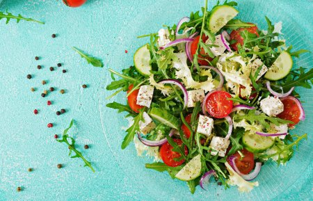 Salad of fresh tomatoes, cucumbers and feta cheese in Greek style. Flat lay. Top view with copy space