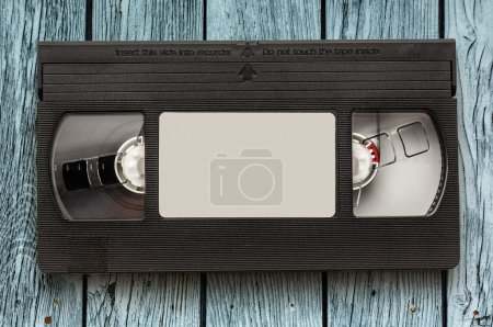 Black video cassette on the wooden background...