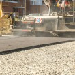 Asphalt-placing machine working on the city road...