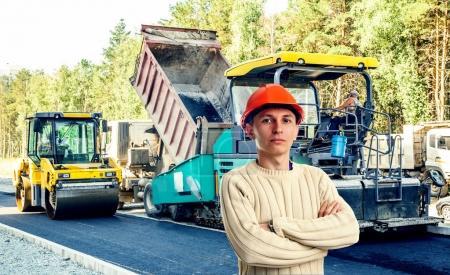 Workman with asphalt-placing machine