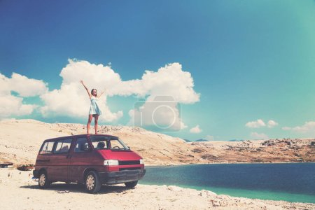 Beautiful tanned girl on a rooftop of a red van