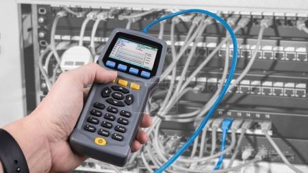 Photo pour Détail de la main masculine lors du test du câblage structuré à l'aide d'un testeur de performance de câble qualifié - image libre de droit