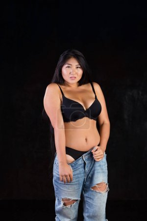 Photo pour Stunningly beautiful curvy Asian girl with long gorgeous hair half dressed on a dark background in alluring, seductive and hot session. - image libre de droit