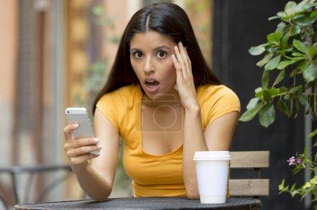 Photo pour Jolie femme latine dans la vingtaine choquée en lisant un message de tex sur son téléphone intelligent à un coffee shop - image libre de droit