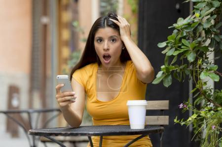 Photo for Attractive latin woman in her twenties shocked while reading a tex message on her smart phone at a coffeeshop - Royalty Free Image