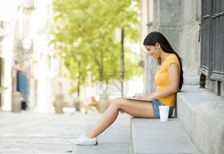 Photo pour Tout au long de la jeune femme brune travaillant sur ordinateur portable assis sur l'escalier, vue de profil - image libre de droit