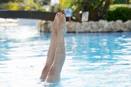 Photo pour Gros plan des pieds d'une femme éclaboussant l'eau dans la piscine - image libre de droit
