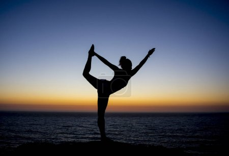 Yoga teacher posing at sunset at the beach with a silhouette back ground