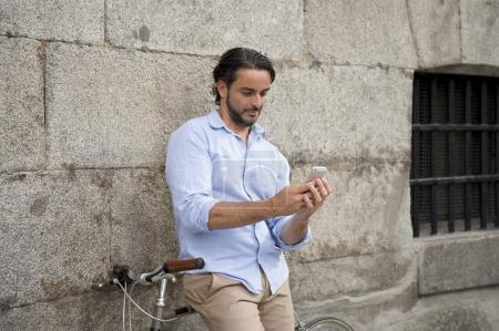 Photo pour Jeune homme heureux de hispanique attrayant en vêtements mode sourire joyeux avec GSM sur vintage vélo rétro cool dans le concept de mode de vie moderne élégant style urbain - image libre de droit