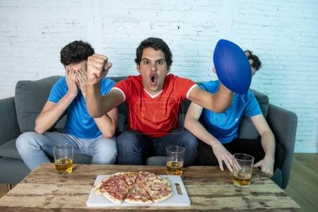 Young group of football fans disappointing and celebrating while watching football game on couch. Young men drinking beer and showing different emotions during watching soccer game