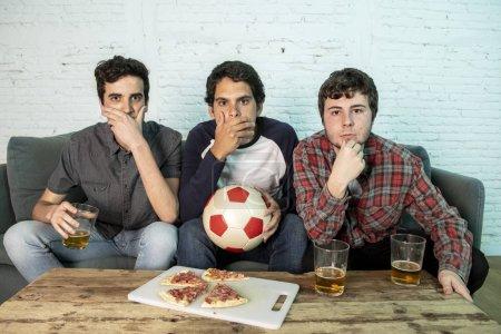 Photo pour Groupe de jeunes supporters décevants tout en regardant le match de football sur canapé à la maison - image libre de droit