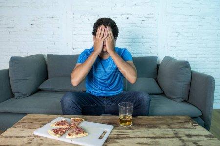 Photo pour Fan de football jeunes décevante au cours de regarder le match de football sur canapé. Homme je regarde le football avec bière et pizza - image libre de droit