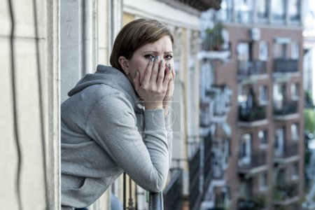Young attractive,red haired, unhappy lonely caucasian woman with depression looking sad on the balcony at home. feeling desperate and hopeless in depression and mental health female concept