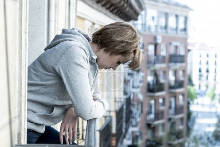young attractive red haired Unhappy suicidal woman suffering from depression feeling desperate, isolated and worthless looking down the street on home balcony. depression and anxiety concept