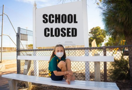 Photo for Covid-19 outbreak schools closures. Sad and bored Schoolgirl kid with face mask feeling depressed and lonely outside her closed school. Restrictions and lockdown as Coronavirus containment measures. - Royalty Free Image