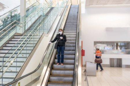 Photo pour COVID-19 Restrictions en cas de pandémie. Une jeune femme attend à l'aéroport pour rentrer chez elle après avoir été coincée dans un pays étranger, car les gouvernements ont restreint les voyages pour arrêter la propagation du coronavirus. . - image libre de droit