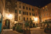 Night view of arch and square with buildings and light of lanterns in Draguignan.