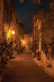 Night view of alley with walls and stone houses in the village of Vence.