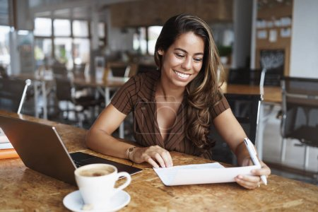 Photo for Happy attractive smiling latino woman sitting cafe, co-working urban space, grining delighted, reading paper and make corrections, prepare for office meeting, sit near opened laptop drink cappuccino. - Royalty Free Image