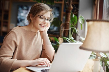 Photo for Cheerful young caucasian girl in glasses using laptop, shopping online or browsing internet, chatting with friends, edit photos for university project, smiling as looking computer screen. - Royalty Free Image