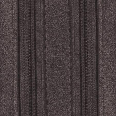 brown leather background, decorated with stitches and zippers. Useful for design-works