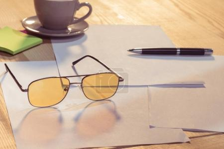 Eyeglasses and blank papers with pen