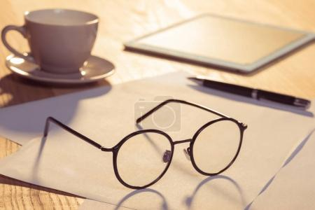 Photo for Close-up view of digital tablet with eyeglasses, cup of coffee and papers on table - Royalty Free Image