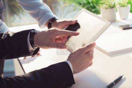 Photo pour Plan recadré de collègues d'affaires utilisant une tablette numérique avec écran blanc - image libre de droit