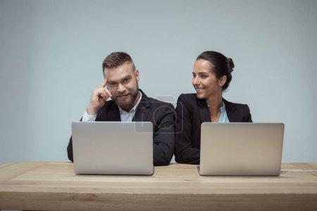 Photo pour Portrait de joyeux collègues utilisant des ordinateurs portables sur le lieu de travail au bureau - image libre de droit
