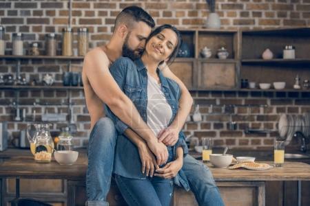 couple hugging en cuisine
