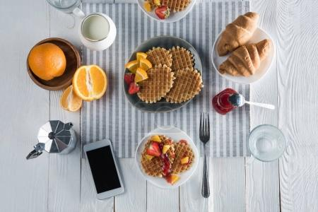 Photo for Top view of fresh tasty breakfast with waffles, coffee and smartphone with blank screen on table - Royalty Free Image
