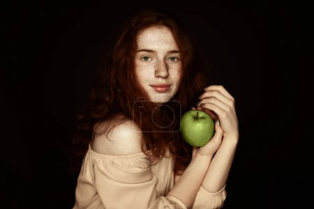 freckled woman holding apple