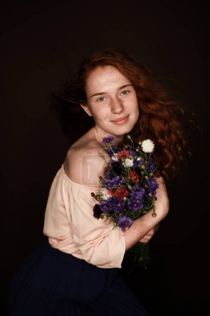 Photo for Smiling elegant redhead girl holding bouquet of cornflowers, isolated on black - Royalty Free Image
