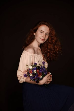 Photo for Beautiful elegant redhead girl posing with bouquet of wild flowers, isolated on black - Royalty Free Image