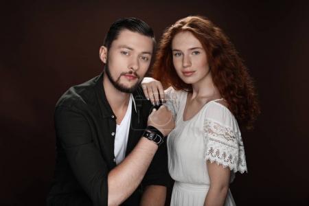 Photo pour Rousse copine et barbu copain posant pour studio shot, isolé sur brun - image libre de droit