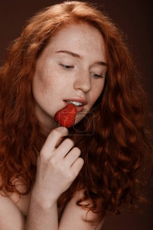 Redhead woman eating strawberry