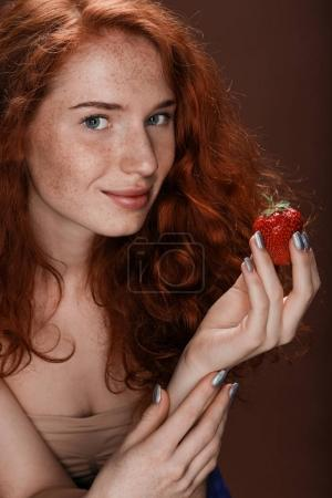 redhead woman posing with strawberry