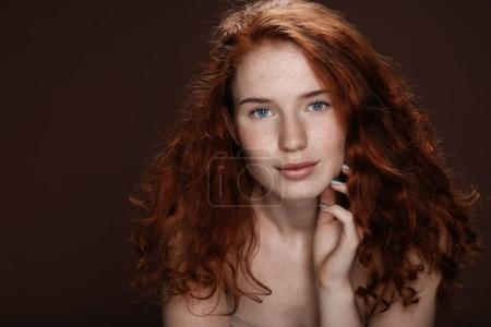 Photo for Tender attractive redhead woman posing for studio shot, isolated on brown with copy space - Royalty Free Image